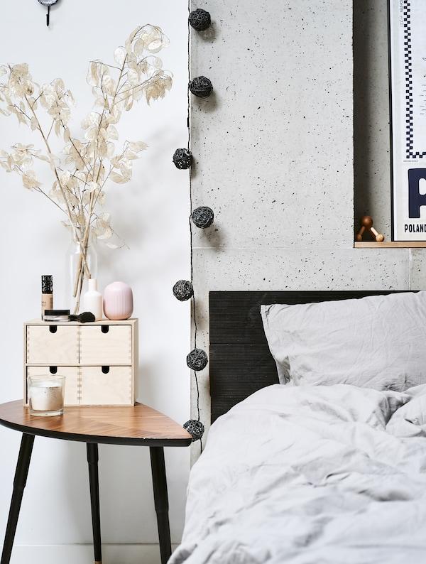Nahaufnahme eines Bettes mit LÖVBACKEN Beistelltisch mittelbraun