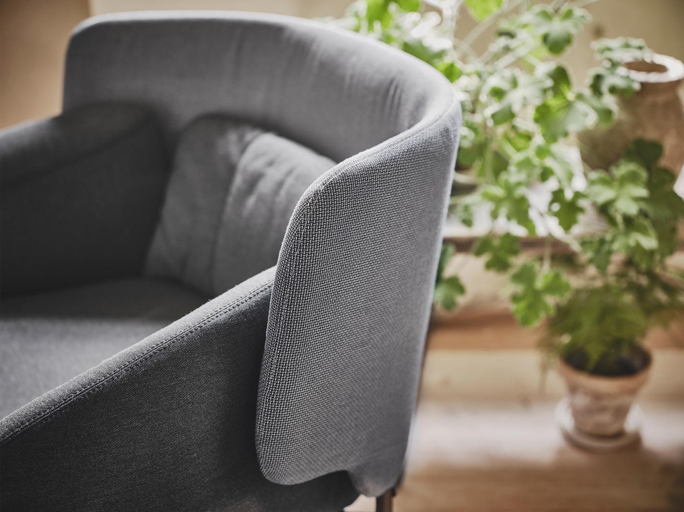 Nahaufnahme eines BINGSTA Sessels mit abgerundeten Armlehnen und einer weit nach vorn geschwungenen, niedrigen Rückenlehne.