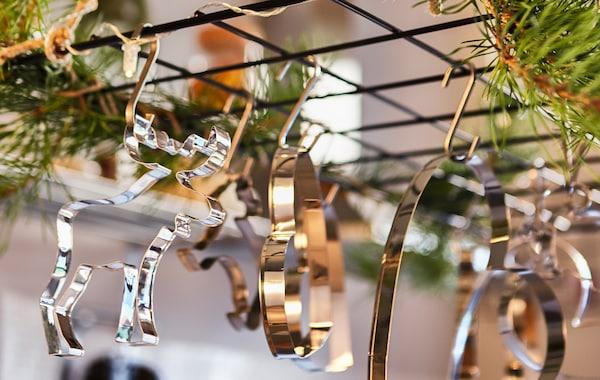 Nahaufnahme eines Drahtspaliers über einer Kücheninsel, dekoriert mit Zweigen und Ausstechförmchen.