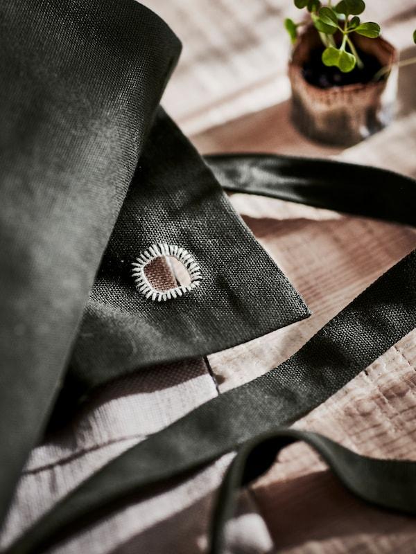 Nahaufnahme eines handgestickten Details auf einer dunkelgrünen Schürze aus Jute. Die Schürze liegt auf einem Tisch neben einer kleinen Pflanze.