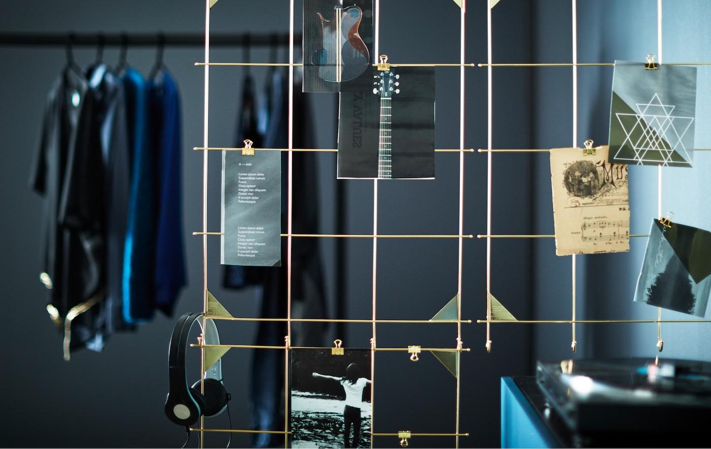 Nahaufnahme eines MYRHEDEN Rahmen in Messingfarben als Raumteiler, an dem Dinge aufgehängt sind