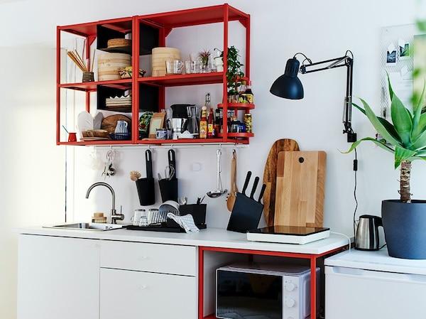 Nahaufnahme eines roten ENHET Wandregals mit ENHET Drehregal für die Küche mit unterschiedlichen Behältern und etwas Ingwer darauf.