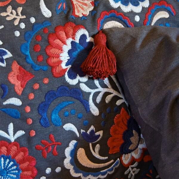 Nahaufnahme eines SKOGSKORN Kissens mit traditionellem Blumenmuster und Verzierungen an den Rändern