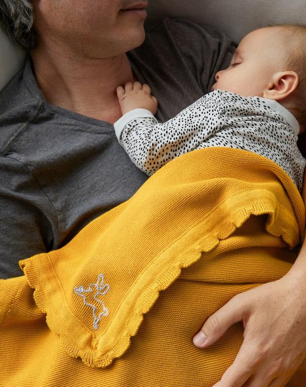 Nahaufnahme eines Vaters mit seinem Baby, das in eine SOLGUL Babydecke eingehüllt ist.