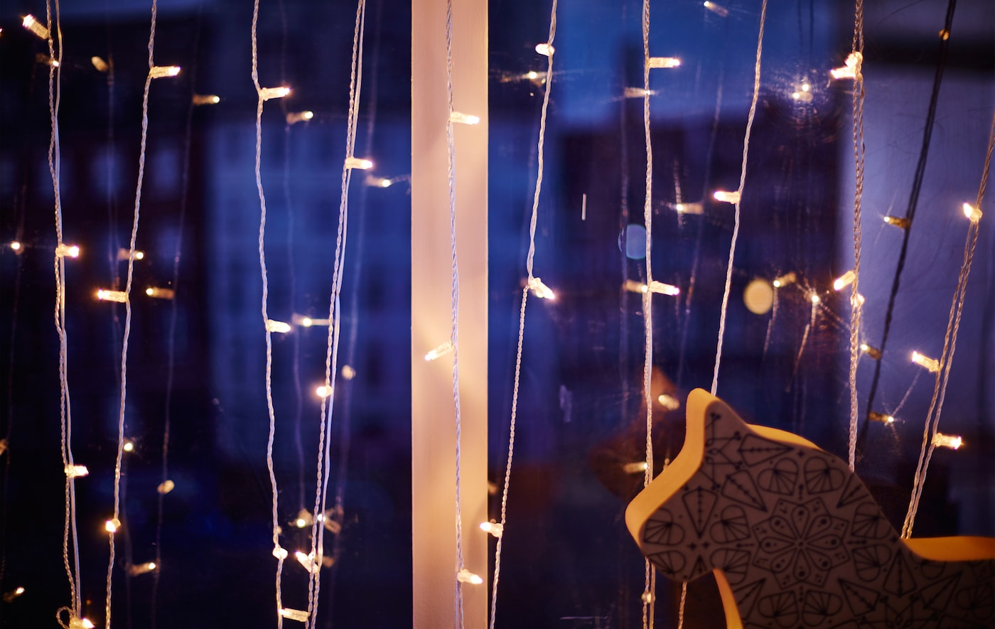 Nahaufnahme eines weißen, baumförmigen Kerzenständers auf einer Fensterbank.