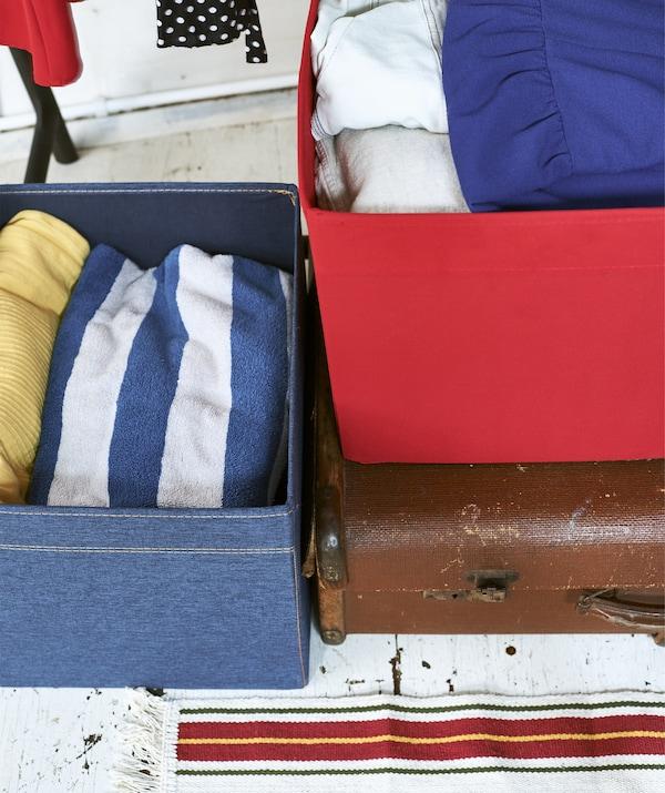Nahaufnahme jeansfarbener und roter Fächer mit Kleidung auf einem Koffer