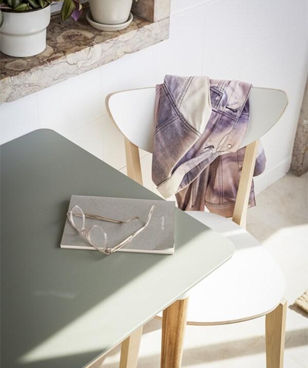 Nahaufnahme von ÅMLIDEN Tischplatte graugrün und einem weißen Stuhl im Sonnenlicht