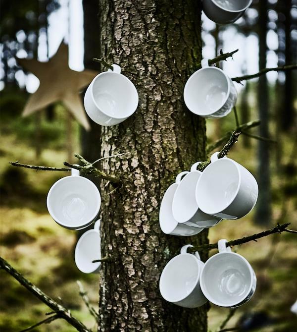 Nahaufnahme von VARDAGEN Bechern in Elfenbeinweiß an den Ästen eines Baumes