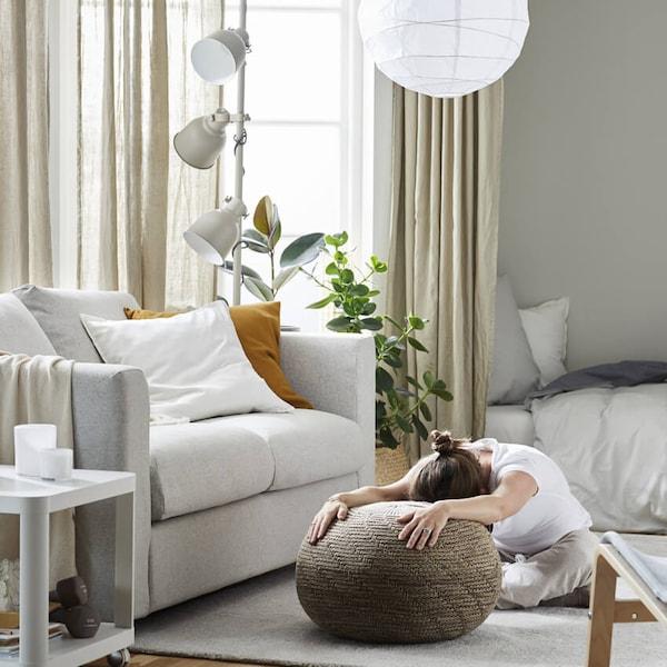 Nainen istuu jalat lotusasennossa olohuoneen matolla ja on kumartunut rahin päälle käden ojennettuna.