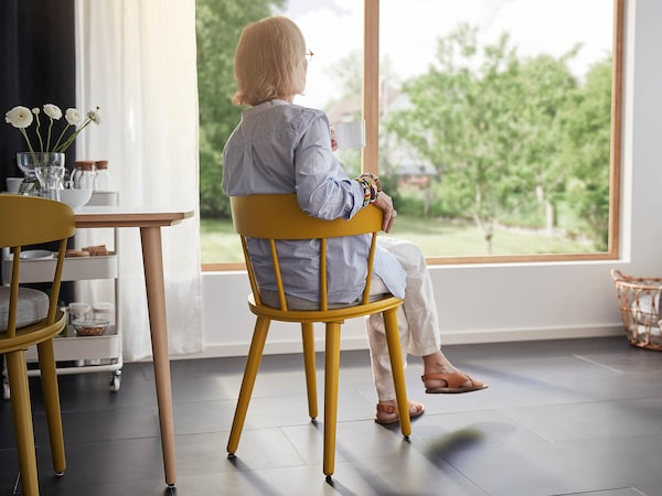 Nainen istuu keltaisella tuolilla