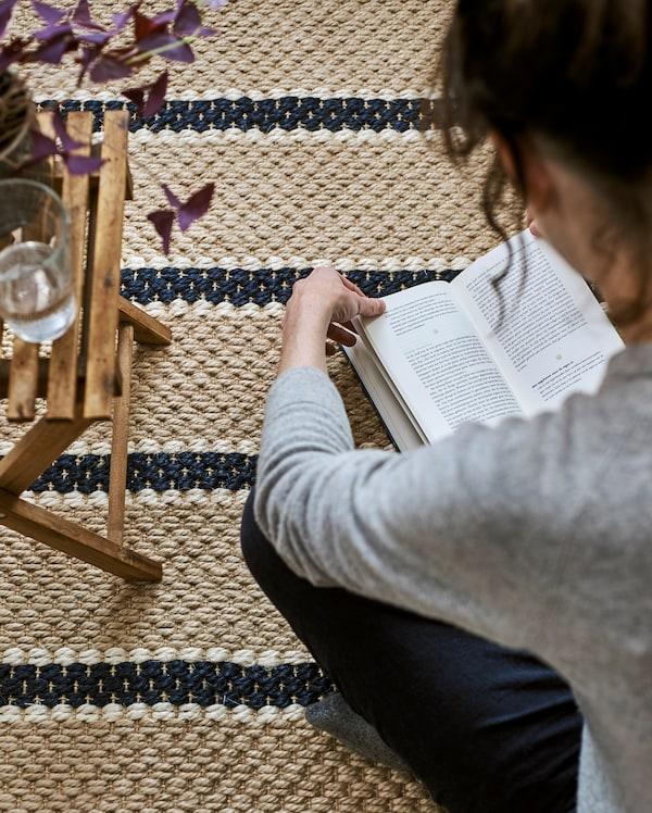 Nainen istuu lukemassa raidallisella matolla, joka on kudottu luonnonkuiduista. Taitettu sivupöytä, kasvi ja lasillinen vettä.