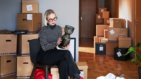 Nainen istuu mustalla tuolilla huoneessa, katsellen lasimaljakkoa käsissään, huonessa on paljon IKEA-muuttolaatikoita.