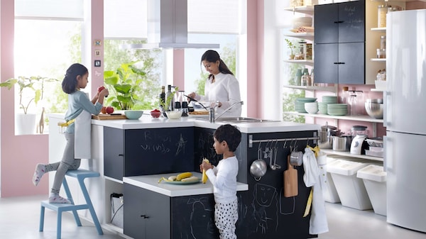Nainen ja kaksi lasta avokeittiössä tekemässä ruokaa.