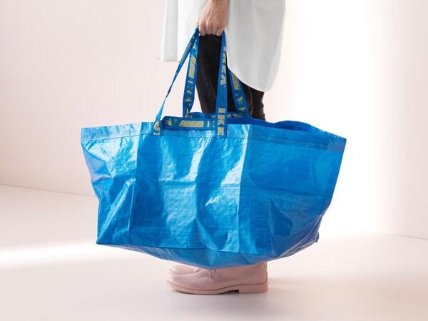 Nainen kantaa sinistä IKEA-kassia