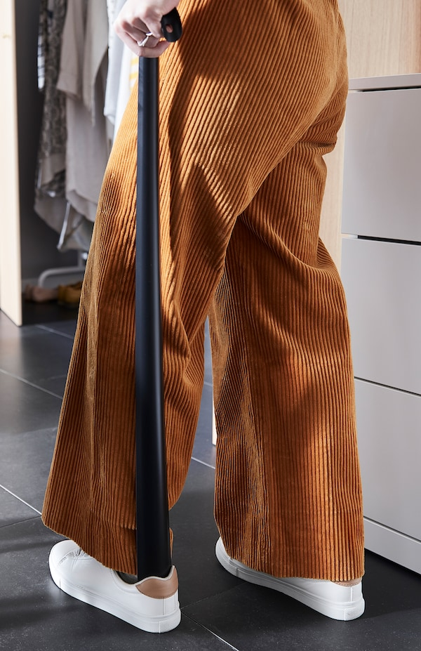 Nainen keltaisissa vakosamettihousuissa pukee kenkiä seisaaltaan OMTÄNKSAM-kenkälusikan avulla.