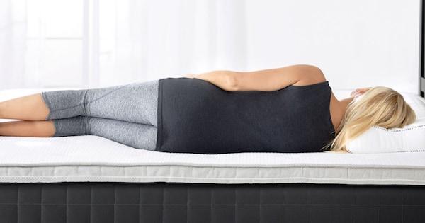 Nainen makaa sängyllä kyljellään, vaaleat verhot ikkunan edessä.