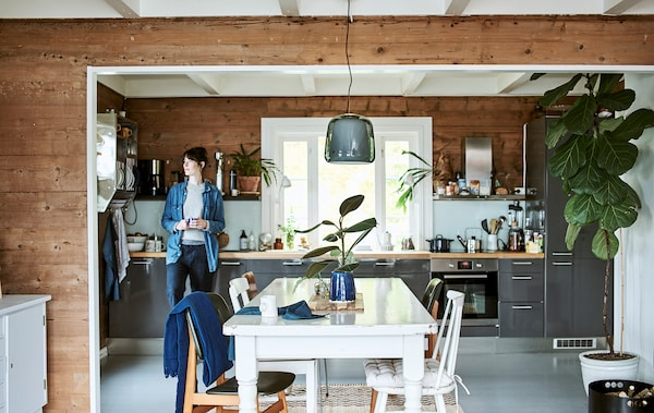 Nainen nojaa kaappiin. Kiiltävä harmaa kaappi avokeittiössä, joka avautuu ruokasaliin. Ruokasalissa on valkoinen puupöytä ja tuolit.