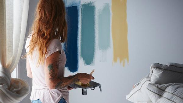 Nainen testaa makuuhuoneen seinään erivärisiä maaleja.