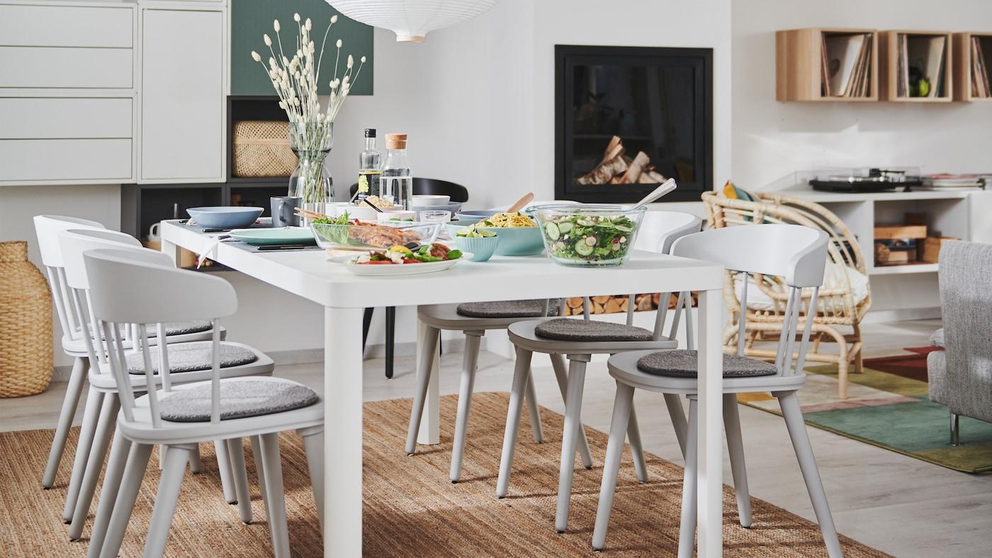 Nappali-étkező belső kandallóval, fali tárolókkal és egy TINGBY étkezőasztallal és OMTÄNKSAM székekkel.