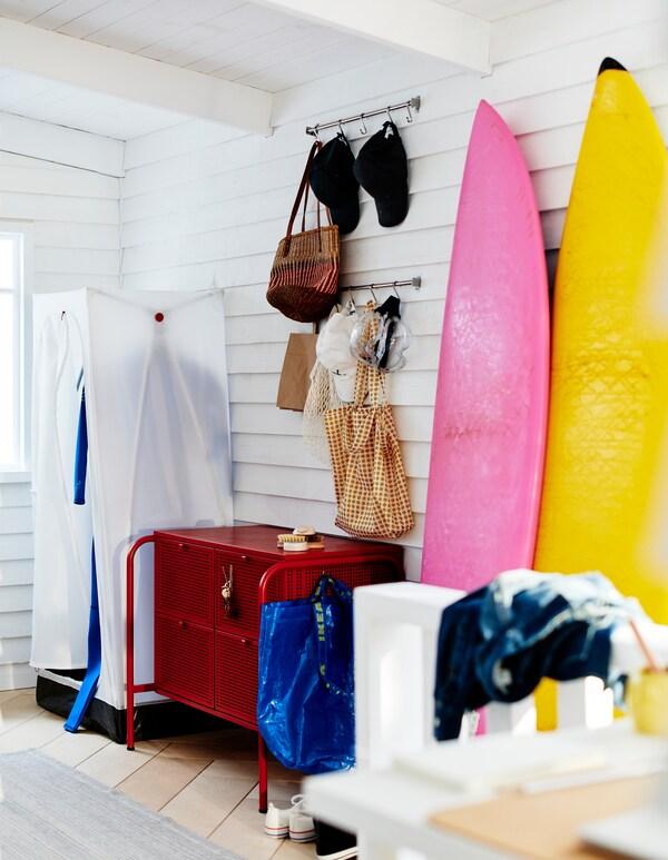 Narożnik białego, wyłożonego boazerią drewnianą pomieszczenia z szafą VUKU, komodą NIKKEBY i opartymi o ścianę deskami surfingowymi.