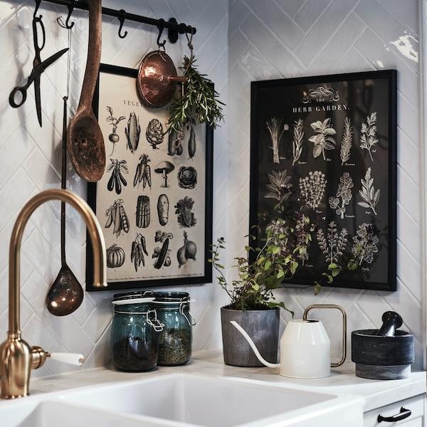Narożnik kuchni z cermaicznym zlewem i ramkmi na ścianie.