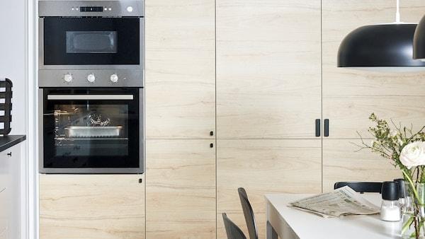 Nástenné kuchynské skrinky IKEA METOD s dvierkami ASKERSUND v so vzorom svetlého jaseňového dreva a vstavanou rúrou a mikrovlnnou rúrou.