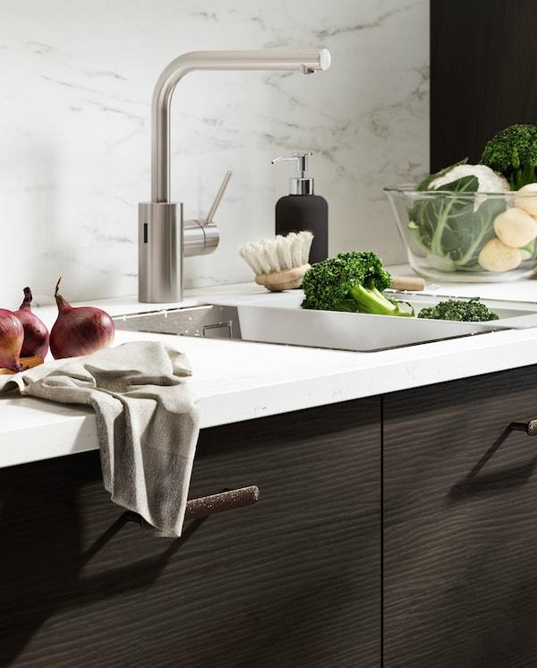 Nástěnný panel se vzhledem bílého mramoru, dřez, utěrka a potraviny připravené na vaření