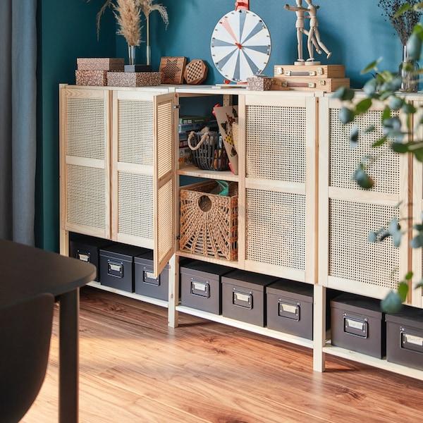 Nástenný úložný diel s otvorenými dvierkami s úložnými škatuľami vo vnútri a ďalšími úložnými škatuľami a doplnkami navrchu.