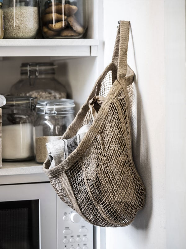 Natural jute basket hung up on a white wall