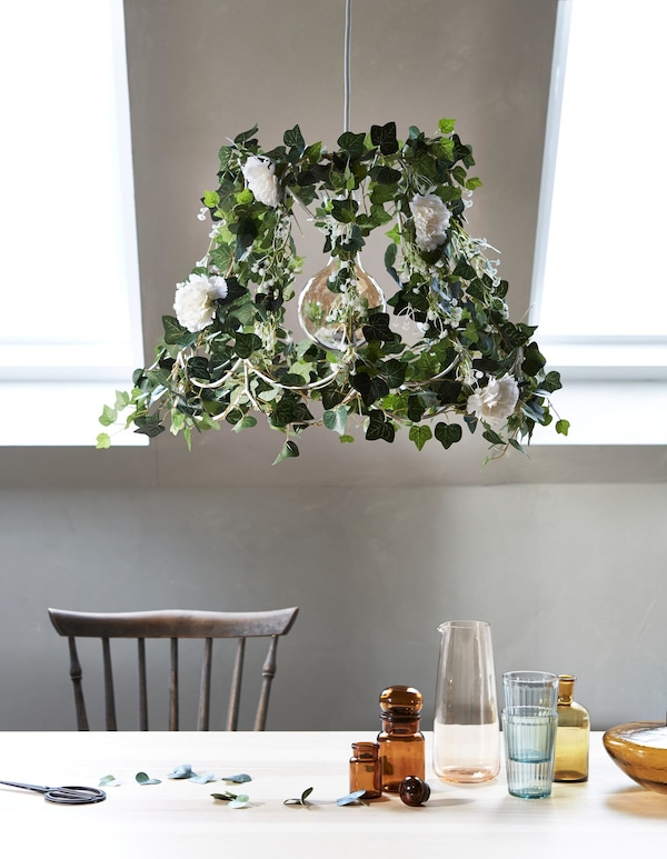 Naturaleza en casa, creada actualizando una lámpara antigua con flores artificiales y plantas verdes, con una mesa en primer plano.