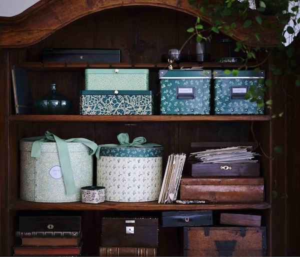 Nature-patterned storage boxes sit inside a wooden cabinet.