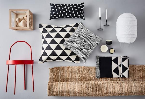 Naturfarbener Teppich, schwarz-weiß gemusterte Kissen & roter Beistelltisch auf grauem Hintergrund
