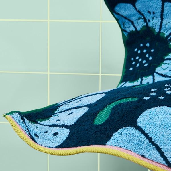 Naufaufnahme von SANDVILAN Handtuch blau/bunt. Zu sehen ist das große Blütenmuster im Jacquardwebstil. Die Kanten des Handtuchs aus 100% Baumwolle sind in Rosa und Gelb eingefasst.