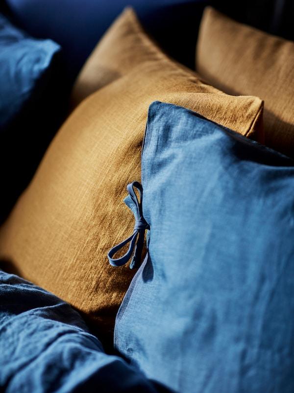 Navlaka koja je ujedno i jastuk na krevetu s plavom PUDERVIVA posteljinom s nekoliko tamnonarančastih ukrasnih jastuka.