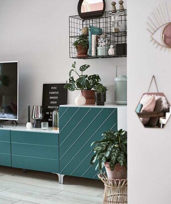 نباتات وتحف على وحدة تلفزيون منخفضة بأبواب خضراء ووحدة رفوف سلكية سوداء على الحائط.