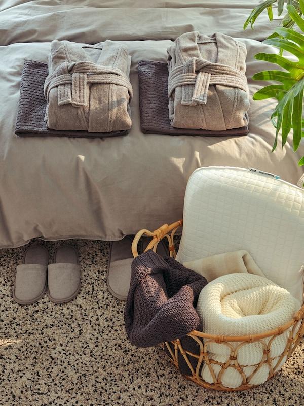 Neatly folded ROCKÅN gray bathrobes in zen bedroom setting with TÅSJÖN gray slippers