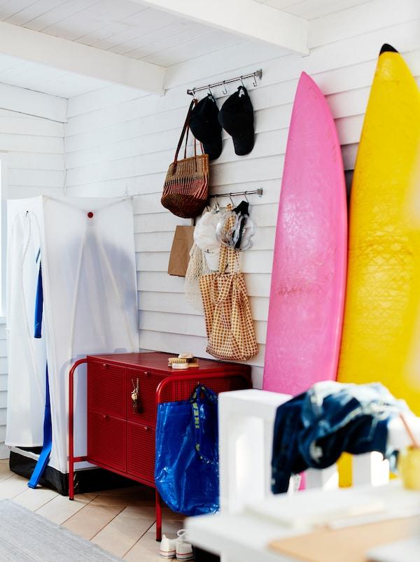 Neformalan hodnik s belim VUKU garderoberom od čelika, tkanine i plastike, i crvenom NIKKEBY komodom s fiokama.