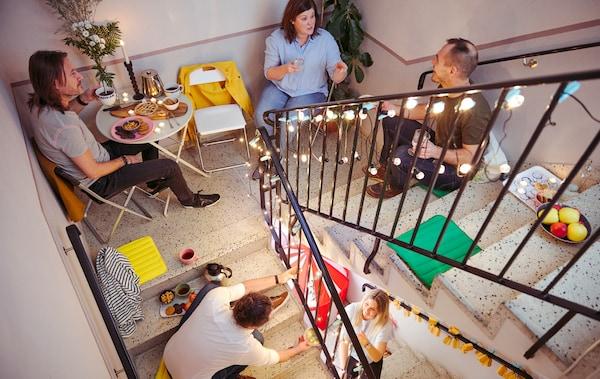 Néhány férfi és nő, beszélgetnek és nassolnak, miközben egy lépcsőház különböző szintjein ülnek.