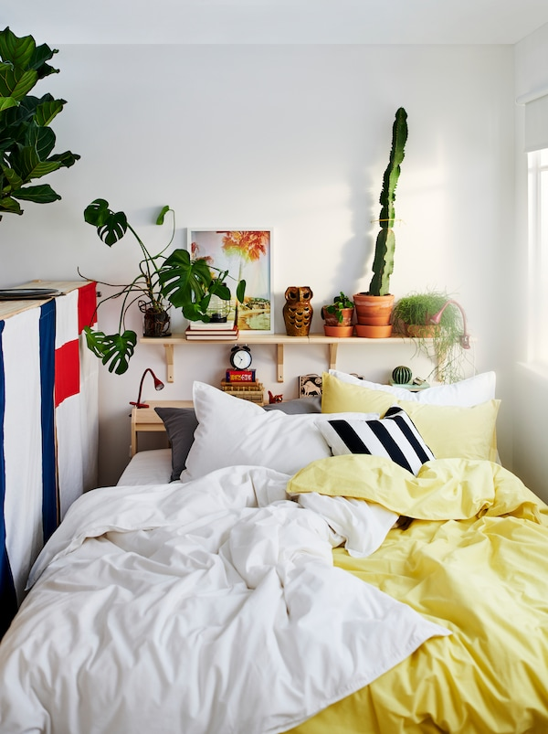 NEIDEN bed with two sets of ÄNGSLILJA bed linen, one yellow and one white. Plants and decorations on a shelf above the bed.