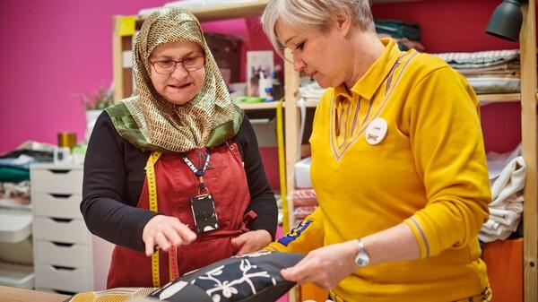 Neire Kerimovska et Karin Wingren discutant d'une housse de coussin dans le cadre de l'initiative Yalla Trappan à Malmö, en Suède.