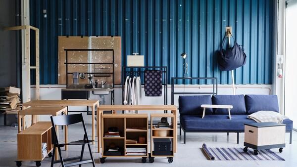 Nejrůznější výrobky kolekce RÅVAROR včetně stolů, pohovky a úložných dílů před stěnou z vlnitého plechu.