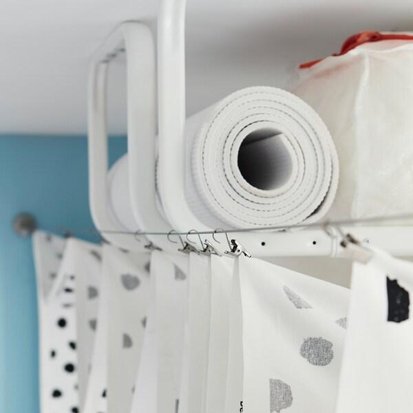 Nekoliko belih MULIG prečaka za kačenje odeće, pričvršćenih za plafon i skrivenih zavesom koja visi između dve žice za zavese.