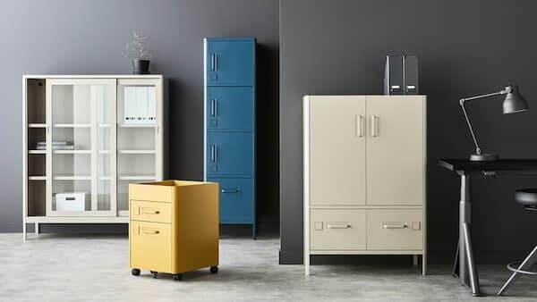 Neljä erilaista IDÅSEN-kaappia vierekkäin. Yhdessä on vieritettävät lasiovet, toisessa valkoiset metalliovet. Yksi pitkä sininen kaappi jossa neljä kaapin ovea päällekäin ja yksi keltainen laatikosto joka mahtuu pöydän alle.