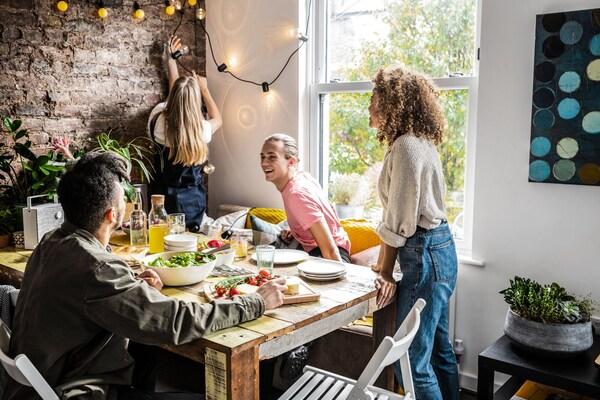 Neljä nuorta ystävystä istuutuu ruokapöytään aurinkoisena päivänä.