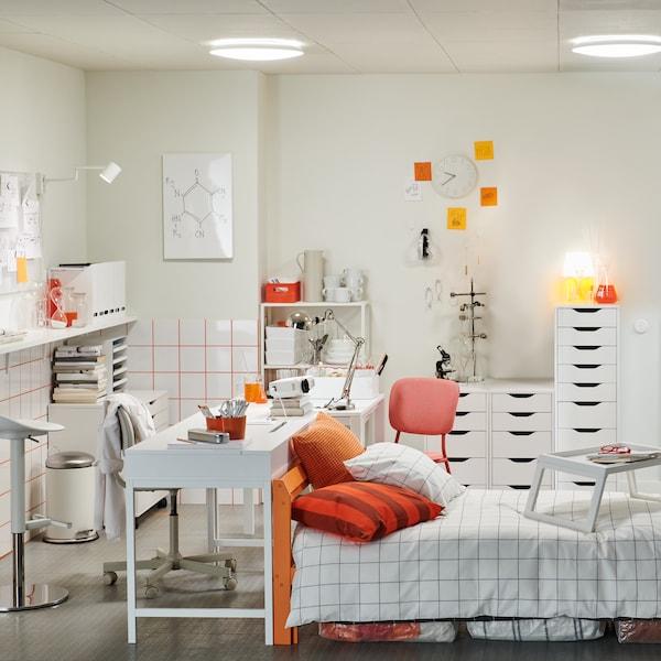 Необычная студенческая комната в бело-оранжевой гамме: кровать, письменный стол, комоды, полки, барный стол и барный табурет.