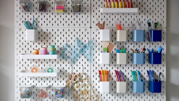 Несколько белых настенных панелей с отверстиями, на которых закреплены разноцветные контейнеры с цветными ручками, скрепками и скотчем.