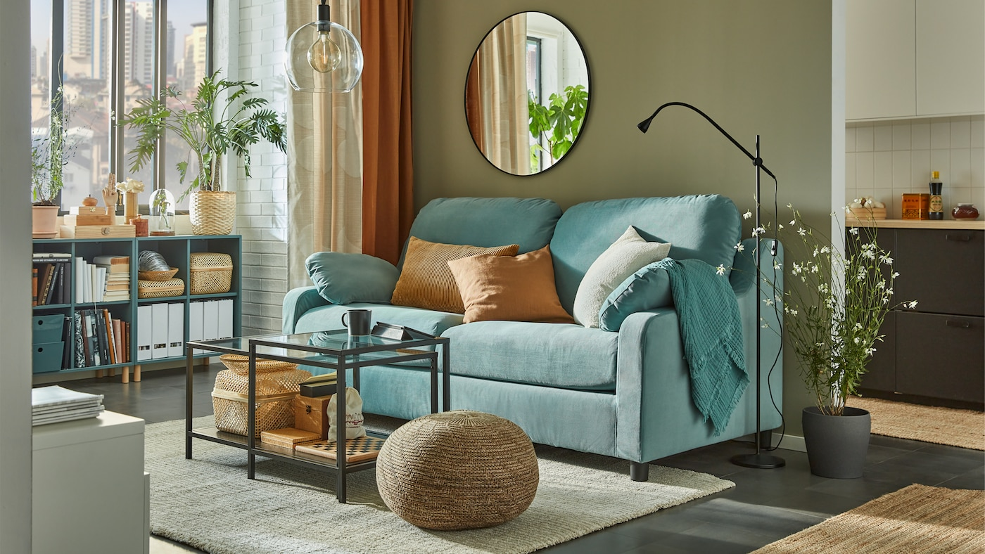 Nesting tables in front of a high-back light turquoise sofa, open cabinets are by the window with books, baskets and files.