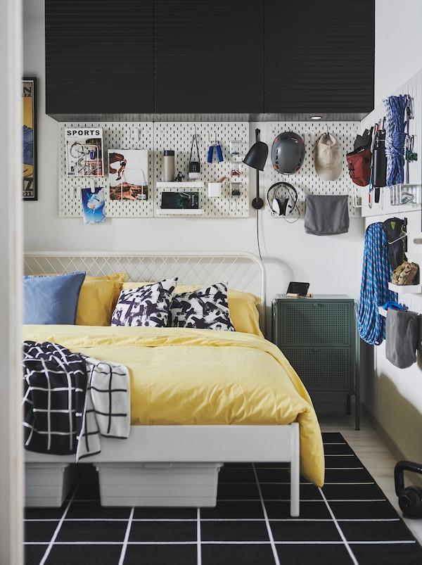 NESTTUN krevet u prostoriji s opremom za planinarenje i mladalačkim ukrasima na SKÅDIS perforiranim pločama na zidovima.