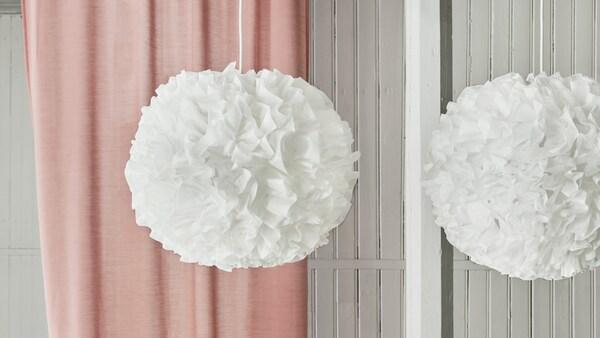 Neue Lampen & Leuchten: Zwei VINDKAST Hängeleuchten in flauschiger Pompom-Form hängen vor einer rosafarbenen Gardine.