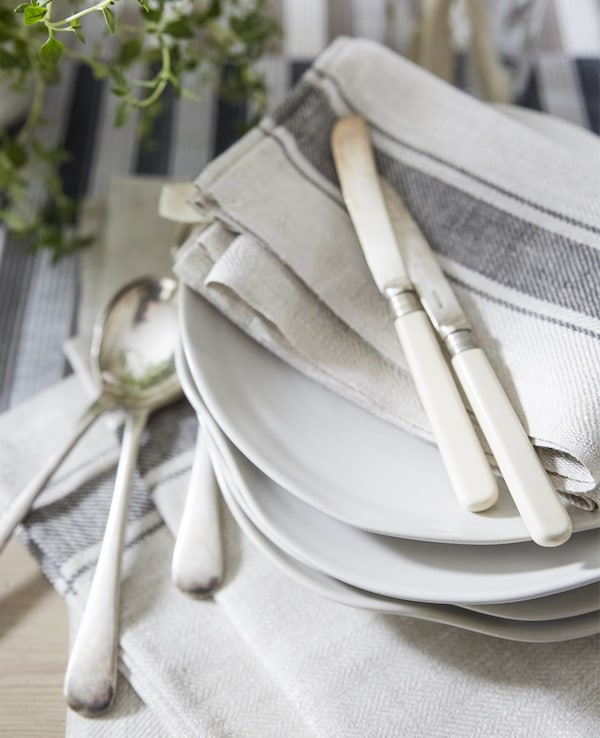 Neutral-coloured cotton napkins and cutlery on a stack of white plates.